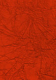 Red background for a design. The compressed silk of red color laying on a table Stock Photos