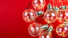 On a red background is a garland of light bulbs. Place for text. On a red background is a garland of light bulbs as well as silver confetti in the shape of stock image