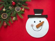On a red background a layout in a corner of fir branches and Christmas ornaments and in the center lies the head of snowman royalty free stock photography
