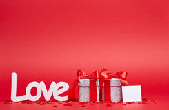 Red background with love sign and gifts Stock Photos