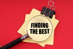 On a red background, a magnifying glass and a sticker with the inscription - Finding the best
