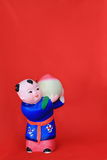 Red background with small clay figurine. Tianjin China clay Zhang Zuopin Stock Photos