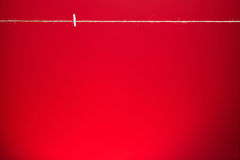 Red background with sting and clothes peg. Red empty background with sting and clothes peg royalty free stock images