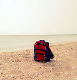 Red backpack on the sandy sea beach, a lot of copyspace Royalty Free Stock Photo