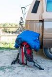 red backpack and sleeping bag near a retro caravan Stock Photos