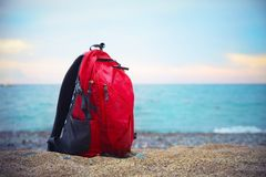 Red backpack for traveling stands on a sandy sea shore on the bl. Red backpack for traveling in focus stands on a sandy sea shore on the blurred seascape Royalty Free Stock Image