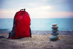 Red backpack for traveling and pyramid of stones stands on a san. Dy sea shore on the blurred seascape background. Traveling concept Stock Photography
