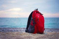 Red backpack for traveling stands from the right of frame on a s. Andy sea shore on the blurred seascape. Close up view Royalty Free Stock Photos