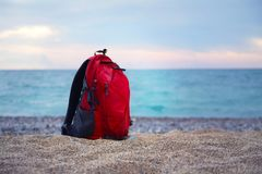 Red backpack for traveling stands on a sandy sea shore on the ba. Ckground of blurred sea. Horizontal Sea landscape. Nobody Stock Image