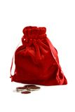 Red bag with coins. Red bag with satin ribbons and coins.  Isolated on white Royalty Free Stock Image
