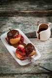 Red baked apples with walnuts and raspberry pouring with chocolate. On a dark wooden background. Autumn or winter dessert Stock Photos