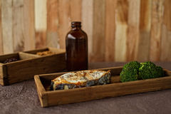 The red baked fish with broccoli, in a wooden posyda, a useful lunch, a dinner, a diet, food. Stock Photography