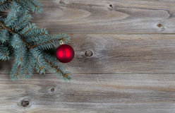 Red Ball Christmas Ornament on Pine Tree Branch with Rustic Wood. Horizontal image of a single red Christmas ornament hanging from a real Blue Spruce tree branch Stock Photography