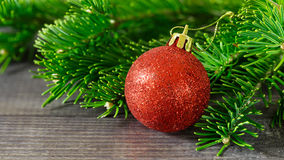 Red ball, Christmas toy, Christmas tree branch on a wooden. Background Stock Images