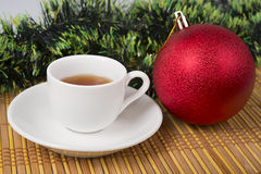Red  ball with cup of tea, new year's decoration Royalty Free Stock Photography