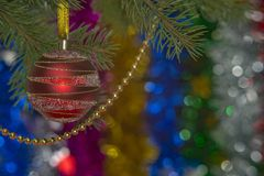 Red ball on Christmas tree with sparkling beads on blurred backg Stock Image