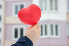 Red ball-heart girl holding in her hand on the background of the urban winter landscape. gift, with love on Valentine`s day royalty free stock photo