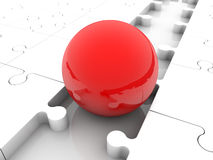 Red ball between puzzle pieces Royalty Free Stock Image