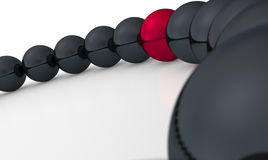 Red ball in row of black ones Stock Photos
