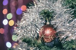Red ball with snowflake on a Christmas tree. In shiny tinsel with beautiful bokeh Stock Image