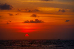 Red Ball of the Sun Dipping towards Horizon at Sunset Royalty Free Stock Image