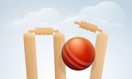 Red ball with wicket stumps for Cricket. Royalty Free Stock Photo