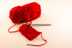 Red ball of wool & crocheting. A few lines of crochet with hook & a red ball of wool Stock Photo