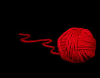 Red ball of yarn on black Royalty Free Stock Photos