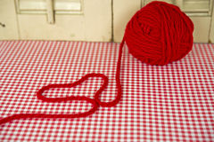 Red ball of yarn with heart. Bright red ball of yarn with heart on red and white gingham Stock Photography