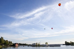 Red Ballons over a bay, Helsinki, Finland. Beautiful summer nordic scene, with red ballons on a clean blue sky, and a red summer cottage in a bay coastline Stock Image