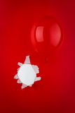 Red balloon. A red balloon against  red background with hole Stock Photo