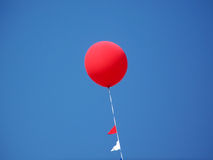 Red Balloon With Blue Sky. Photograph of a large red balloon flying in a beautiful blue cloudless sky Royalty Free Stock Images