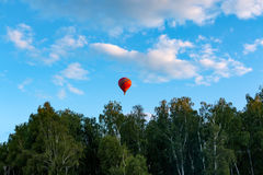 Red balloon flies over the blue clear sky Stock Images