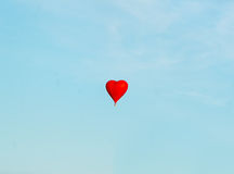 The red balloon floats in heavens. Red balloon in the blue sky wuth forest in the down Royalty Free Stock Photo