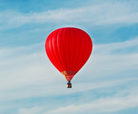 The red balloon floats in heavens. Red balloon in the blue sky wuth forest in the down Royalty Free Stock Image