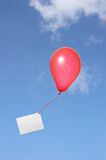 Red balloon with greeting card in the sky. A red floating balloon with a ribbon and a greeting card on blue sky with clouds stock photo