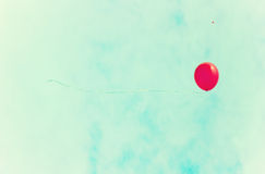 Red balloon over a retro sky Stock Photo