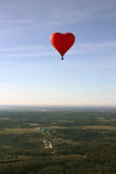 Red balloon in the shape of red heart hovers over the terrain Stock Image