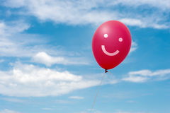 Red balloon in the sky. Red balloon with smile in the blue sky royalty free stock photography