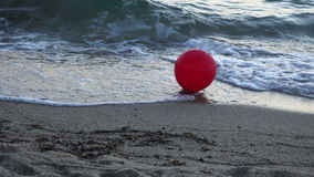 Red balloon with a white heart hit by waves 4K. Stock footage stock video