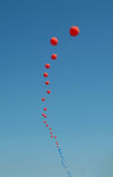 Red balloons. Red and blue balloons strung together against sky Stock Photo