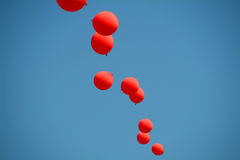 Red balloons. Red and blue balloons strung together against sky royalty free stock images