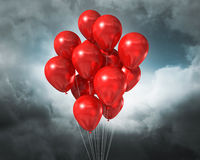 Red balloons on a cloudy dramatic sky Royalty Free Stock Photography