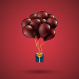 Red balloons raised a gift box. Depicted on red Stock Photo