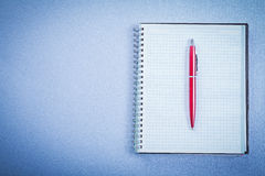 Red ballpoint pen on blank notepad office concept Stock Photos
