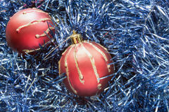 Red balls in blue tinsel Royalty Free Stock Images