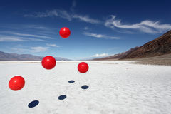 Red balls in death valley. Red balls randomly bouncing in death valley stock photos