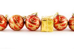 Red balls and gift. A few red balls and one gold gift on the white background royalty free stock photography