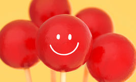 Red balls of lollipops on stick vase with hand drawn smile face in red vase Stock Photos