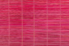 Red bamboo mat, wooden background Stock Photo